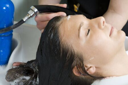 womanliness: brunette in a salon getting washed her hair with shampoo