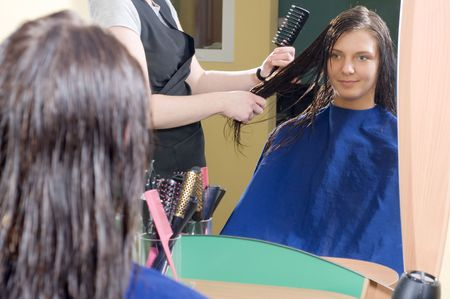 nice girl in a beauty salon while an hair stylist brush and dry her hair photo