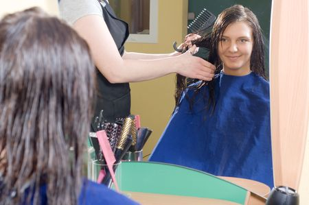 nice girl in a beauty salon while an hair stylist brush and dry her hair Stock Photo - 2584483