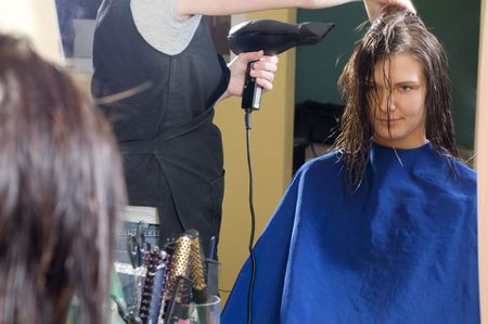 nice girl in a beauty salon while an hair stylist brush and dry her hair Stock Photo - 2584497
