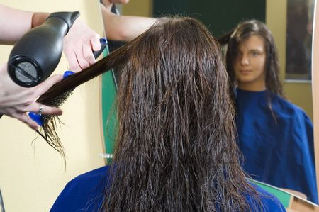 nice girl in a beauty salon while an hair stylist brush and dry her hair Stock Photo - 2582907