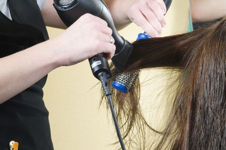 womanliness: close up of girl head in beauty salon while an hair stylist brush and dry her hair