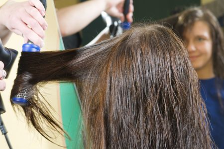 womanliness: nice girl in a beauty salon while an hair stylist brush and dry her hair Stock Photo