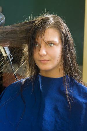 nice girl in a beauty salon while an hair stylist brush and dry her hair Stock Photo - 2582905