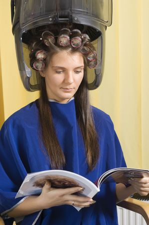 young woman sitting under a hairdryier with roller on head Stock Photo - 2584489