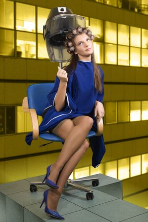 young woman sitting under a hairdryier with roller on head Stock Photo - 2582884