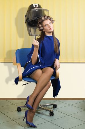 young woman sitting under a hairdryier with roller on head  photo