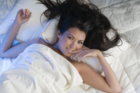 cute brunette in bed with hair on pillows and a finger on lips photo
