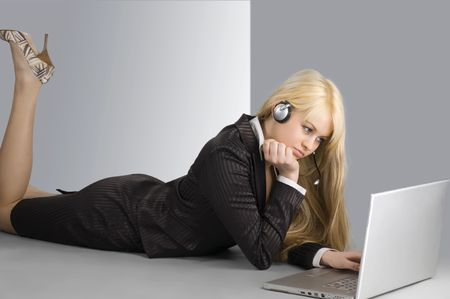 attractive blond girl laying down on the floor working on a laptop photo