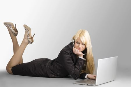attractive blond girl lawing down on floor working with laptop photo