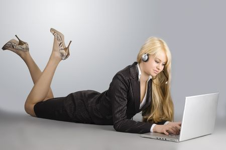 attractive blond girl working on a laptop on the floor photo