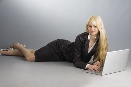tailleur: attractive blond girl on the floor working on a laptop with earphone