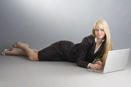 attractive blond girl on floor working on a laptop with earphone  photo