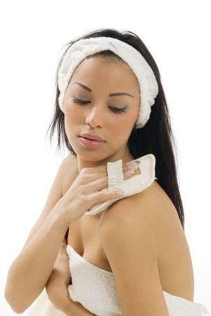 cute brunette wearing beige towel scrubbing herself with a sponge photo
