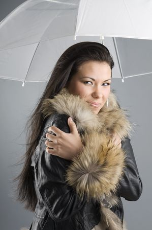 pretty brunette with fur jacket and white umbrella warming herself photo