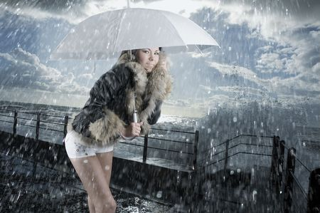 short wave: cute brunette near the sea in rough water and under rain