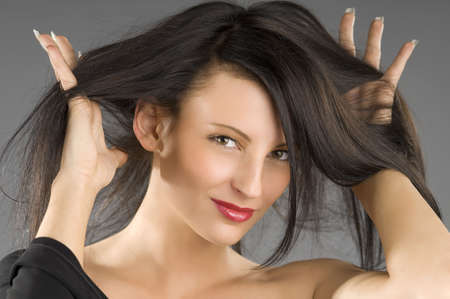 cute brunette with the hands between hair and red lips photo