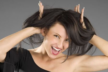 young and nice brunette with hands between hair screaming photo
