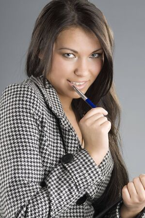 tailleur: cute girl in formal dress looking in camera sexy and playing with pen Stock Photo