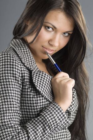 cute girl looking with sensual look and a pen near mouth photo