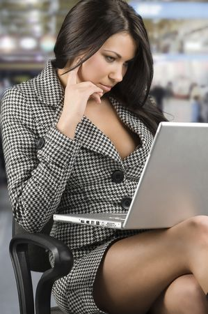 sensual secretary in formal dress with laptop on her legs Stock Photo
