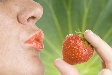 red mouth with lipstick giving a kiss at a strawberry Stock Photo - 3083799