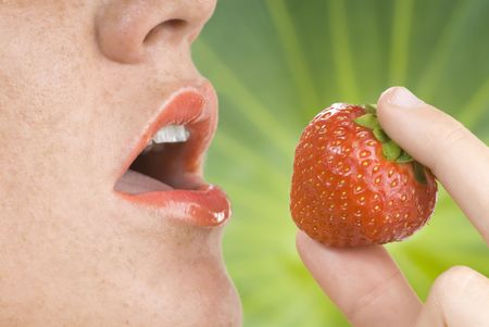 open mouth with red lipstick and a strawberry near focus on strawberry Stock Photo - 3083801