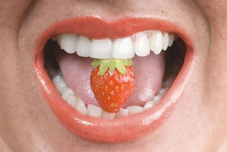 lápiz de labios rojo abierto la boca con una fresa entre los dientes  Foto de archivo - 3083802
