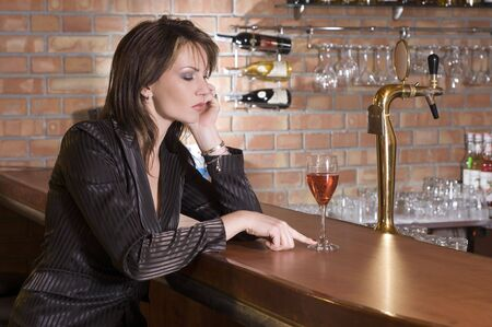 woman sitting down in a pub with a red drink thinking Stock Photo - 3083869