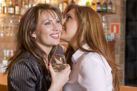 two attractive woman near a bar drinking and talking about their secrets Stock Photo - 3083875