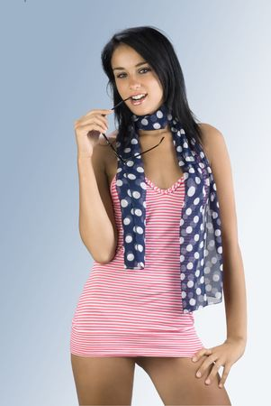 cute and sensual brunette wearing a red beach dress and blue foulard with white dot