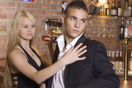 blond girl and a boy near the bar drinking a cocktail focus on the boy Stock Photo - 3307786