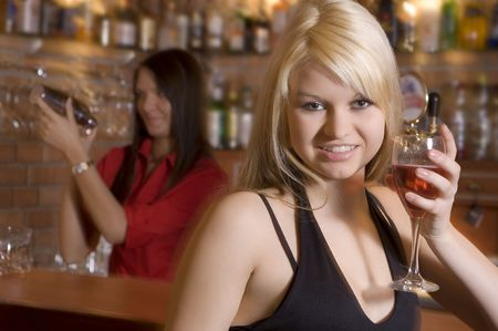 blond girl near the bar drinking a cocktail photo