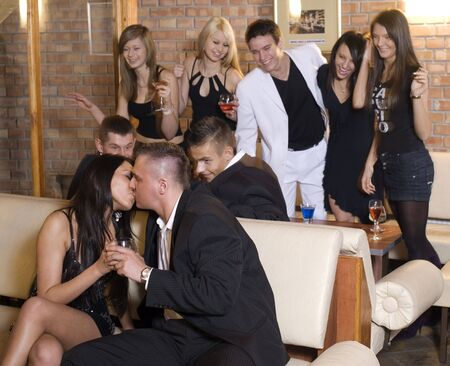 young couple kissing with friends behind loughing in moving focus on the couple photo