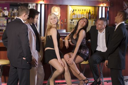 people partying: a group of young people sitting near the bar inside a night club