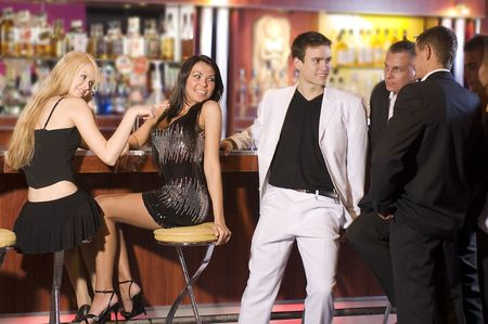 a group of young people siiting near the bar inside a nigh club