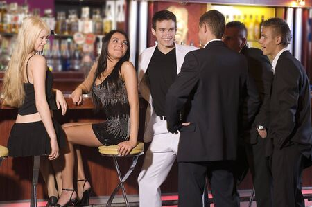 a group of young people siiting near the bar inside a nigh club photo