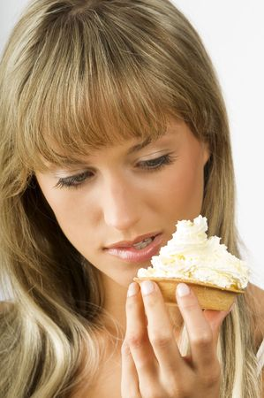blond nice girl eating a dessert with a lot of cream Stock Photo - 3307793