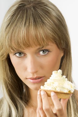 blond nice girl eating a dessert with a lot of cream Stock Photo - 3307796