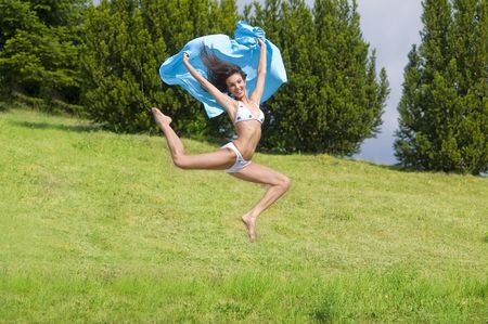 young woman jumping in a field with a blue scarf and white bikini Stock Photo - 3430786
