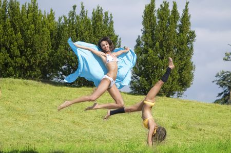 two girls jumping and stretching their body in a field Stock Photo - 3430779