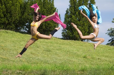 two great girls jumping tougheter in a field with pink and blue scarfe Stock Photo - 3430791