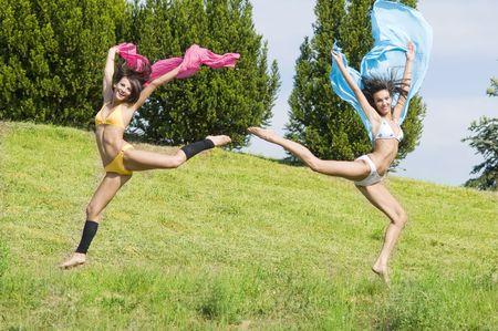 two great girls jumping tougheter in a field with pink and blue scarfe Stock Photo - 3430796