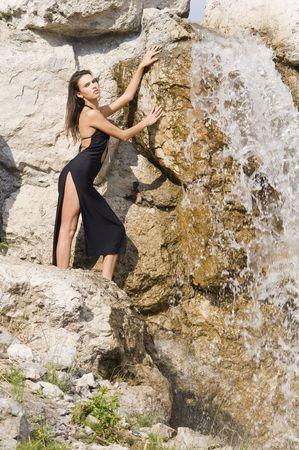 fashion portrait of a very cute brunette in black sexy dress near waterfall Stock Photo - 3430797