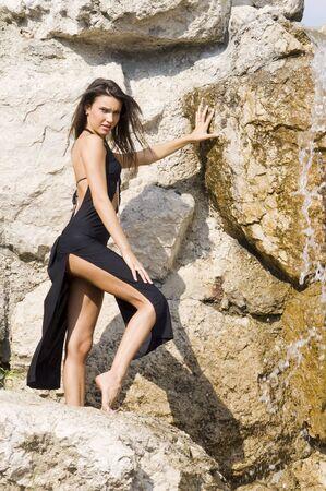 fashion portrait of a very cute brunette in black sexy dress near waterfall Stock Photo - 3430789