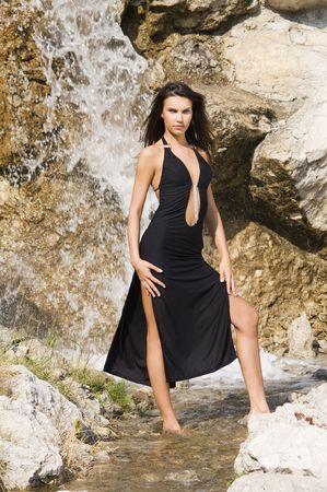 fashion portrait of a very cute brunette in black sexy dress near waterfall Stock Photo - 3430783