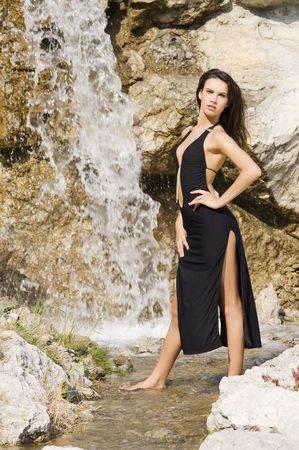 sensual brunette in fashion pose with black dress in front of a waterfall Stock Photo - 3430781