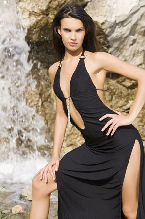 sensual brunette in fashion pose with black dress in front of a waterfall Stock Photo - 3430793
