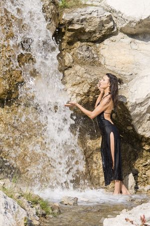 sexy brunette in black elegant dress taking shower in a waterfall Stock Photo - 3430816