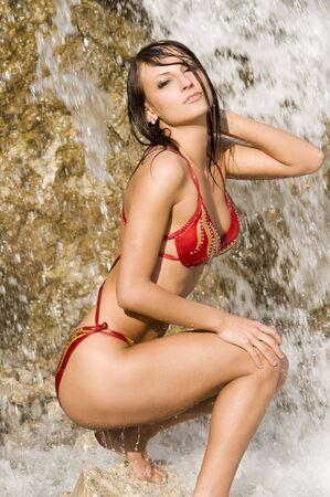 cute brunette in red bikini playing with water near the waterfall Stock Photo - 3430807